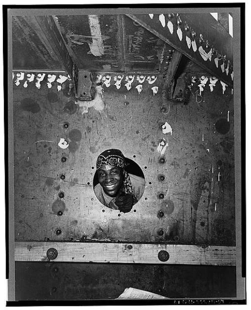 Building the SS Frederick Douglass. Smiling from the porthole is rivet heater Willie Smith. (Photograph by Roger Smith, Office of War Information, Library of Congress Prints and Photographs Division)